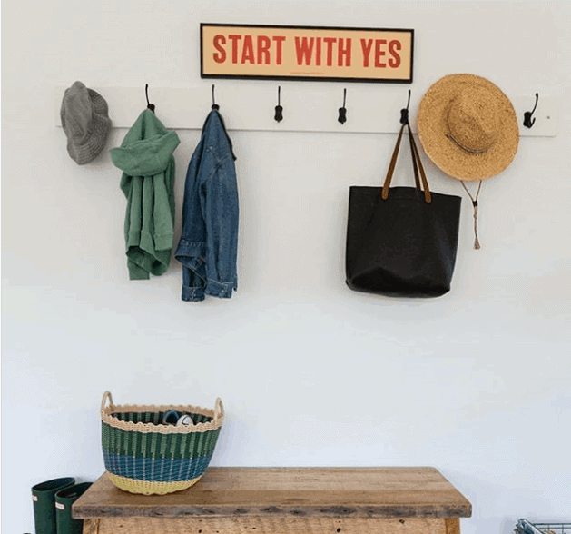 A rustic bench, hooks, fun artwork make this makeshift mudroom pop.