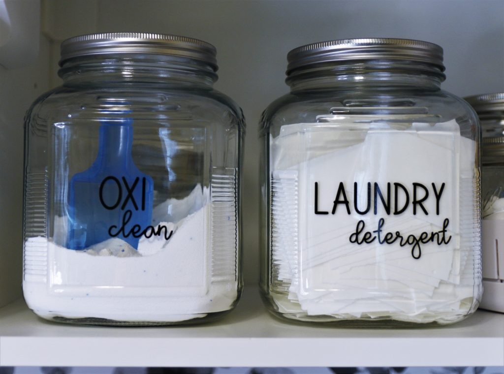 Laundry room organization is essential. Putting detergent in glass jars makes your laundry room pretty, too.