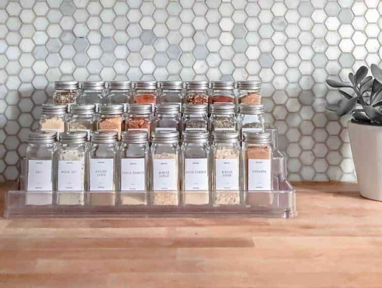 Best Ideas for Organizing Spices: In matching jars arranged in a tiered stand with matching labels as artwork on counter.